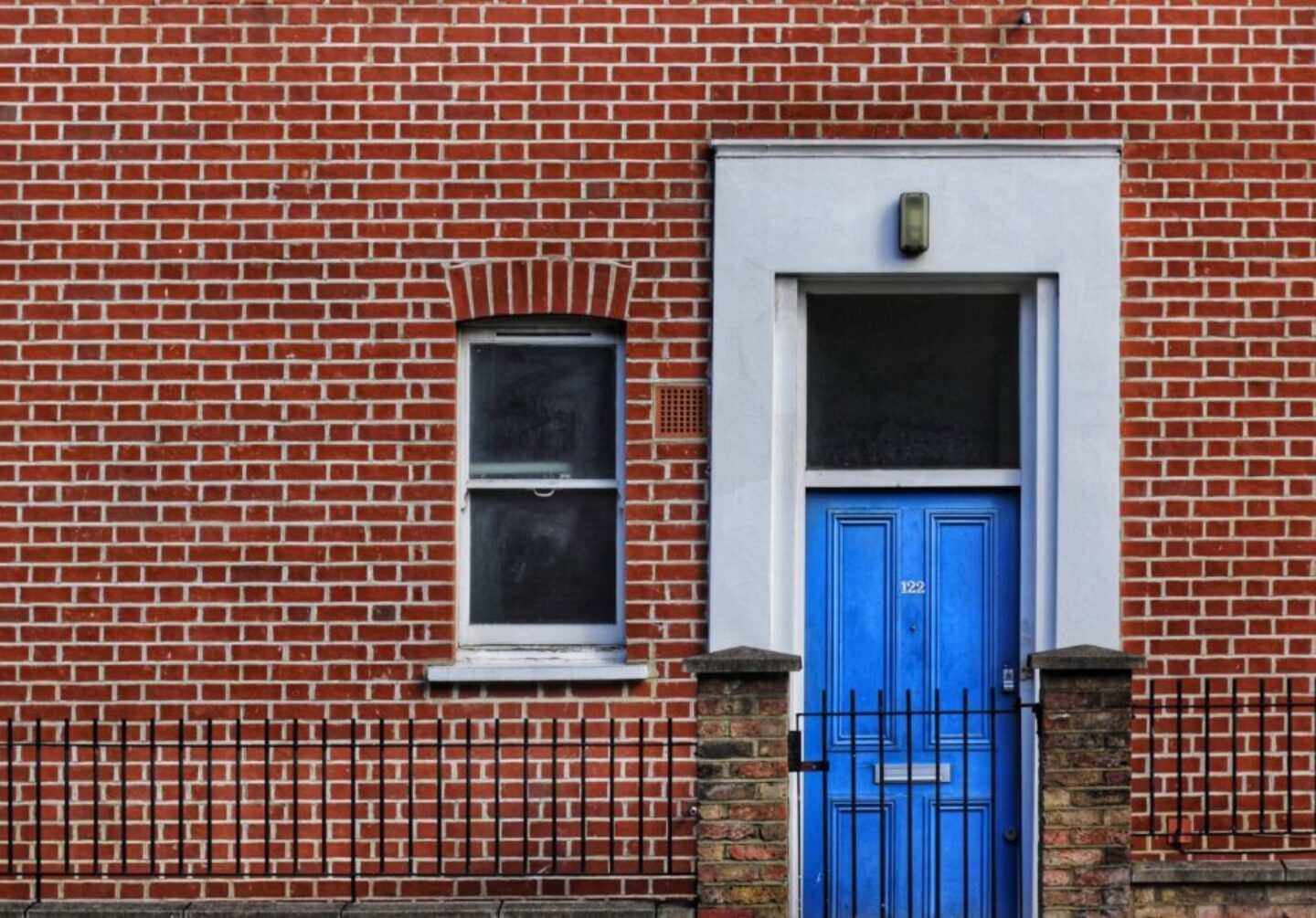 red brick building with closed door and window